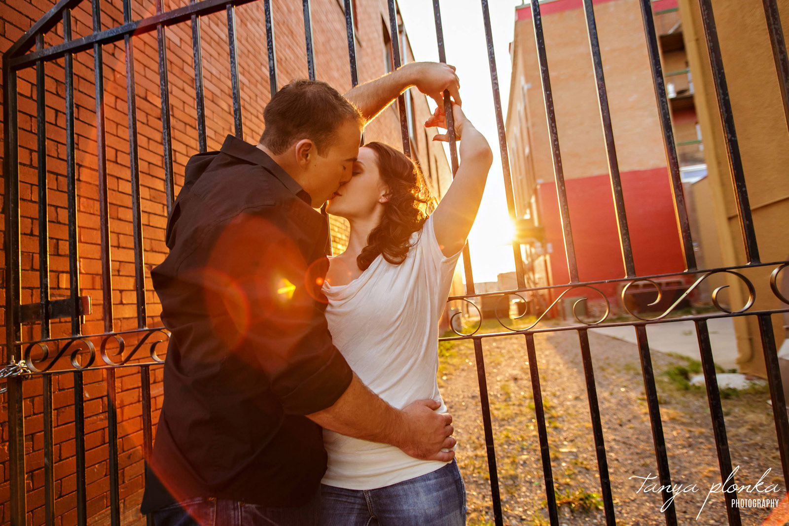 couple kisses in downtown Lethbridge with sun flare around them