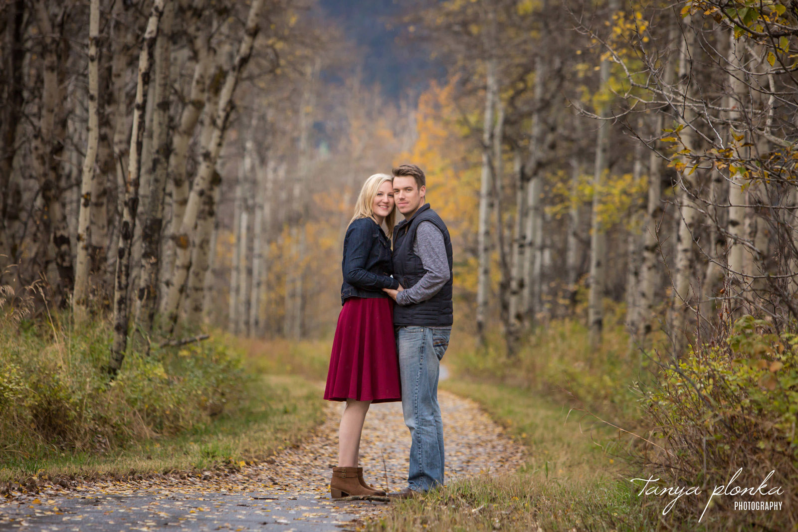 couple stands together on path in Waterton during the fall