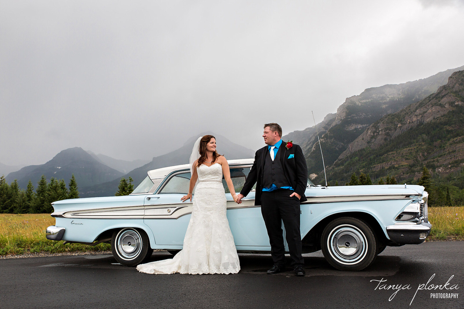 wedding couple stand in front of blue classic car in Waterton