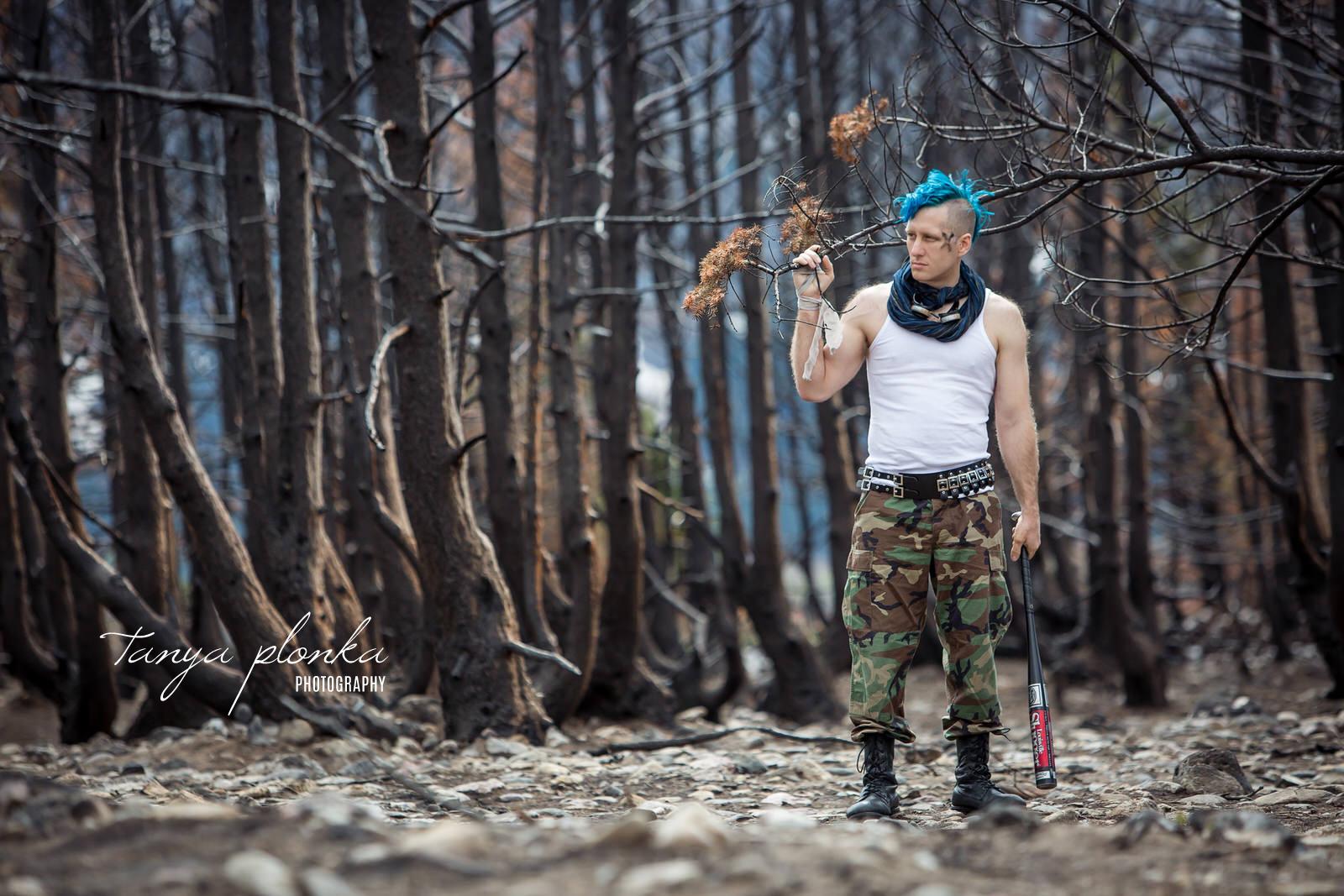 man dressed as wasteland raider holding baseball bat in burnt forest in Waterton