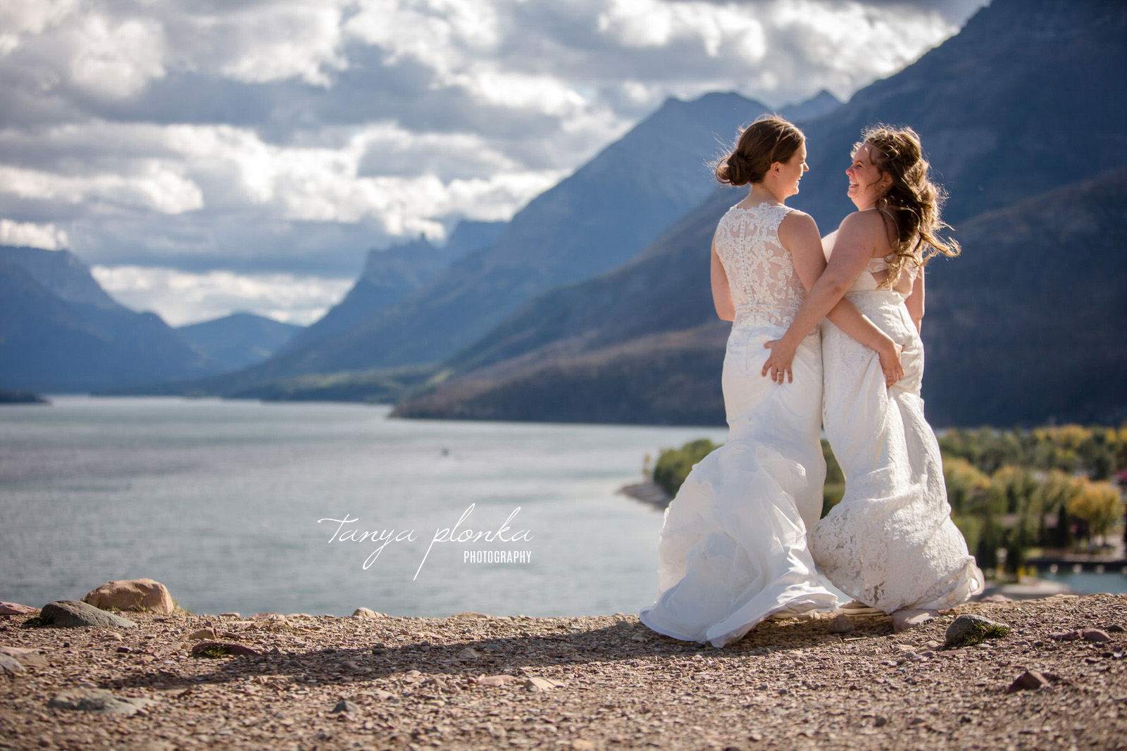 brides laugh while grabbing each others butts with view of Waterton mountains