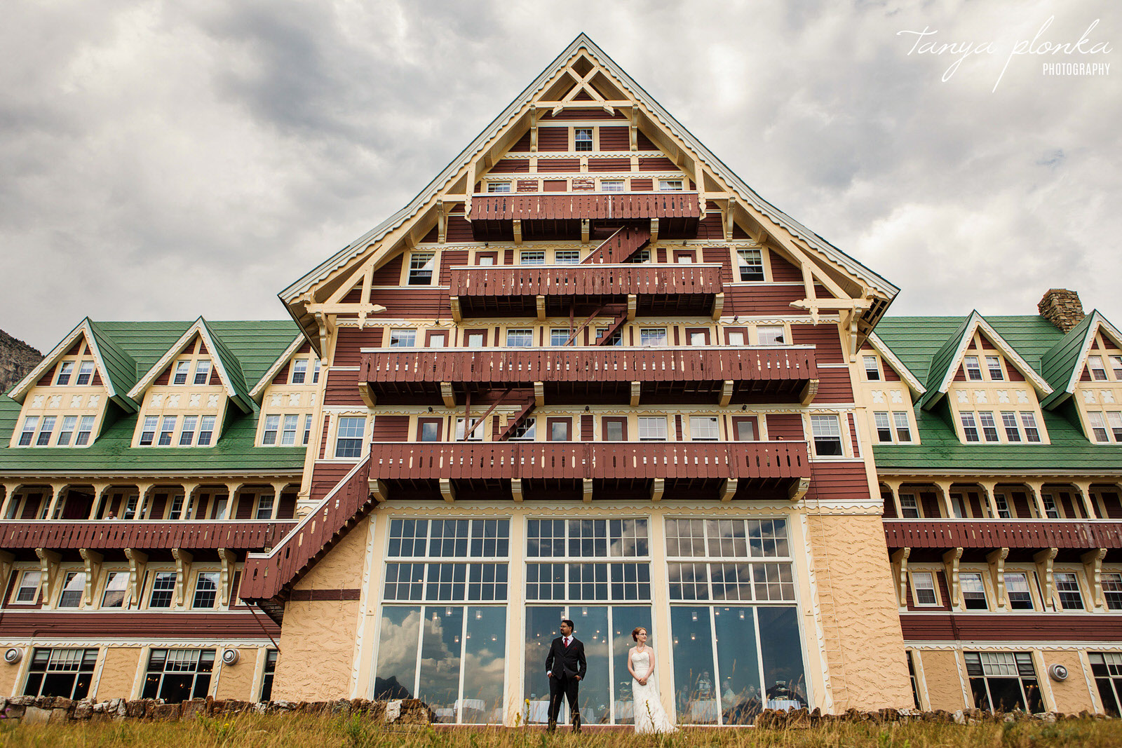 dramatic photo of bride and groom standing in front of Prince of Wales Hotel on rainy day in Waterton