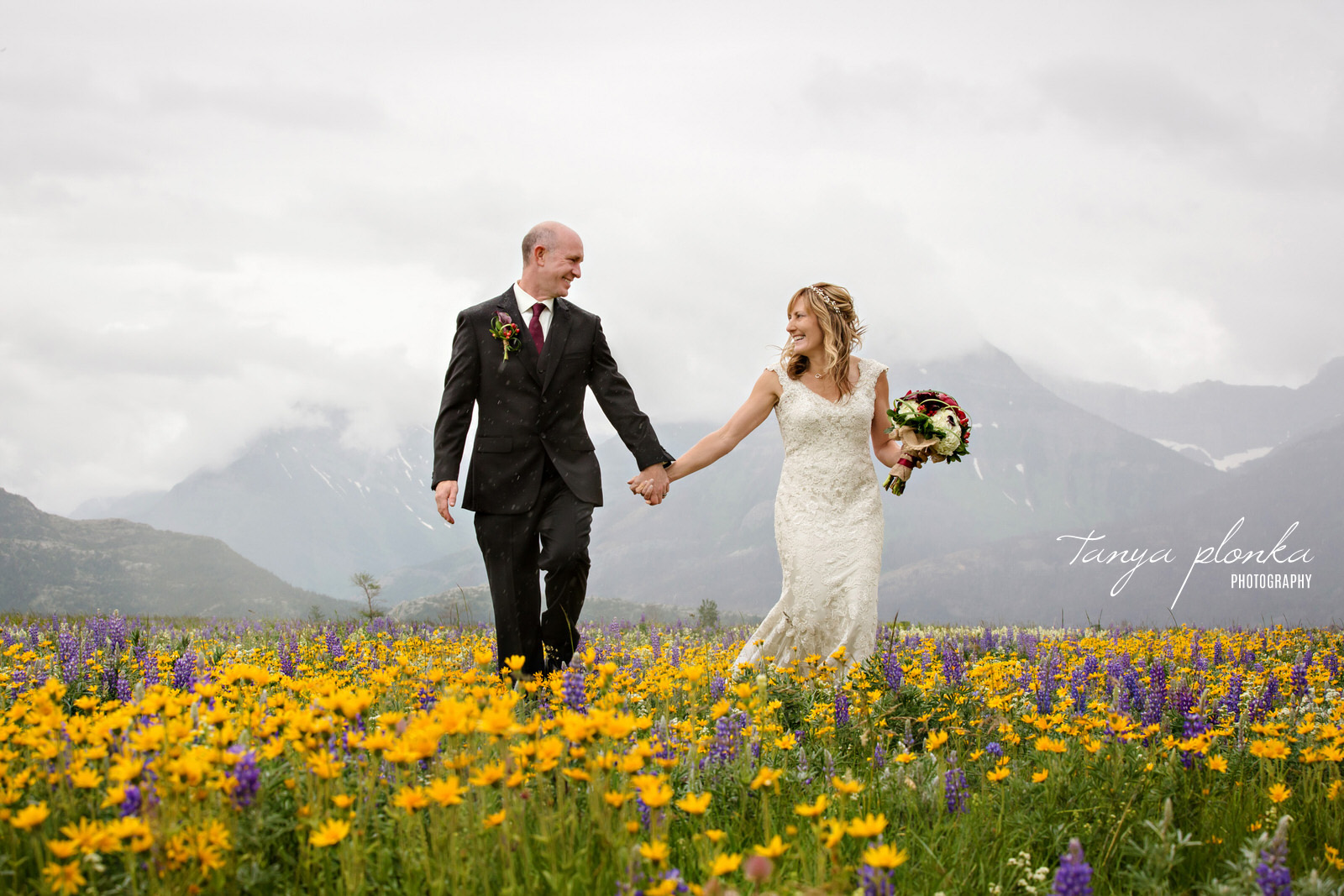 groom and bride walk through field of yellow and purple wildflowers with mountains in background while holding hands