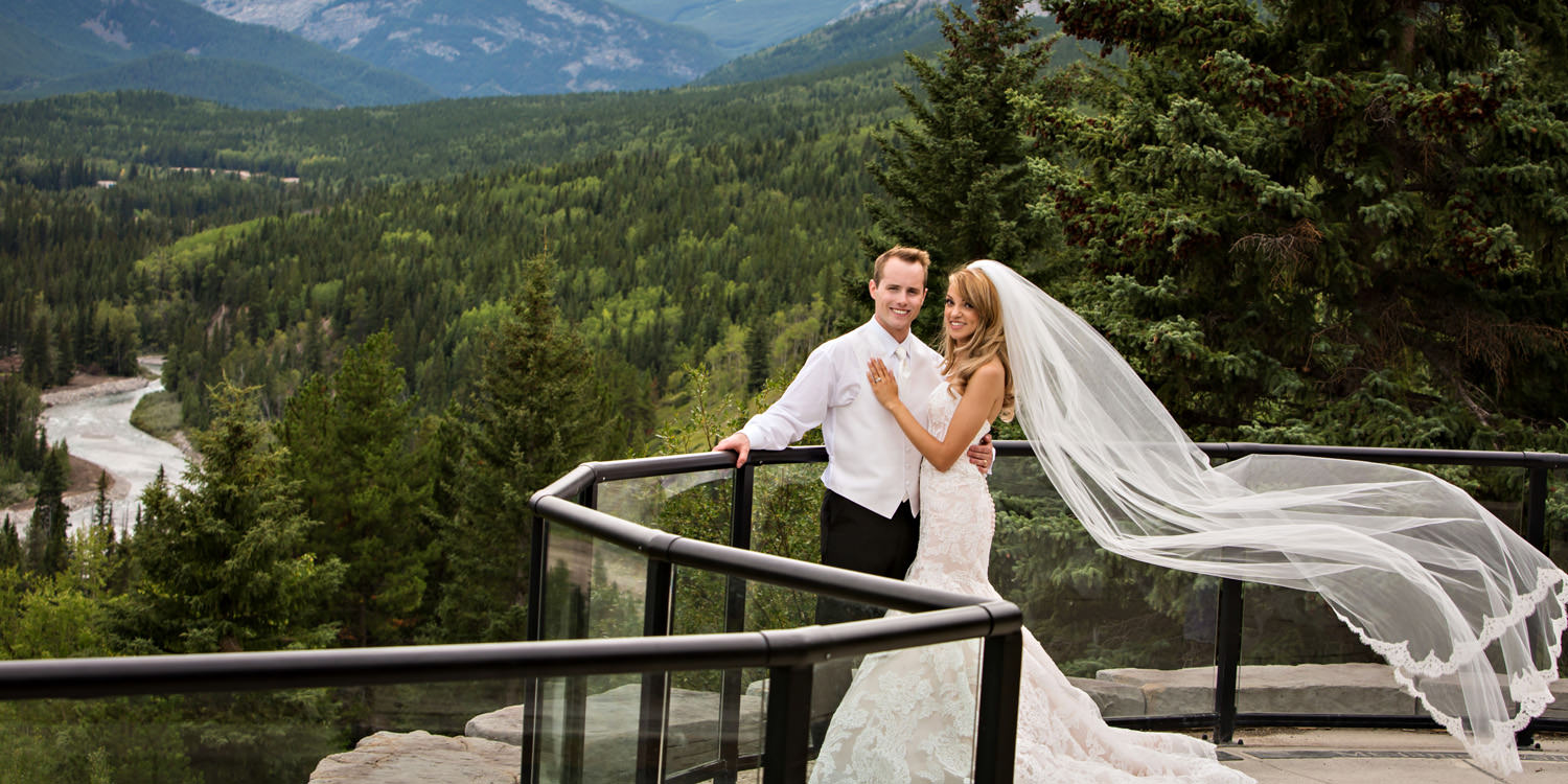 Bride and groom overlooking river in Kananaskis with veil blowing in wind