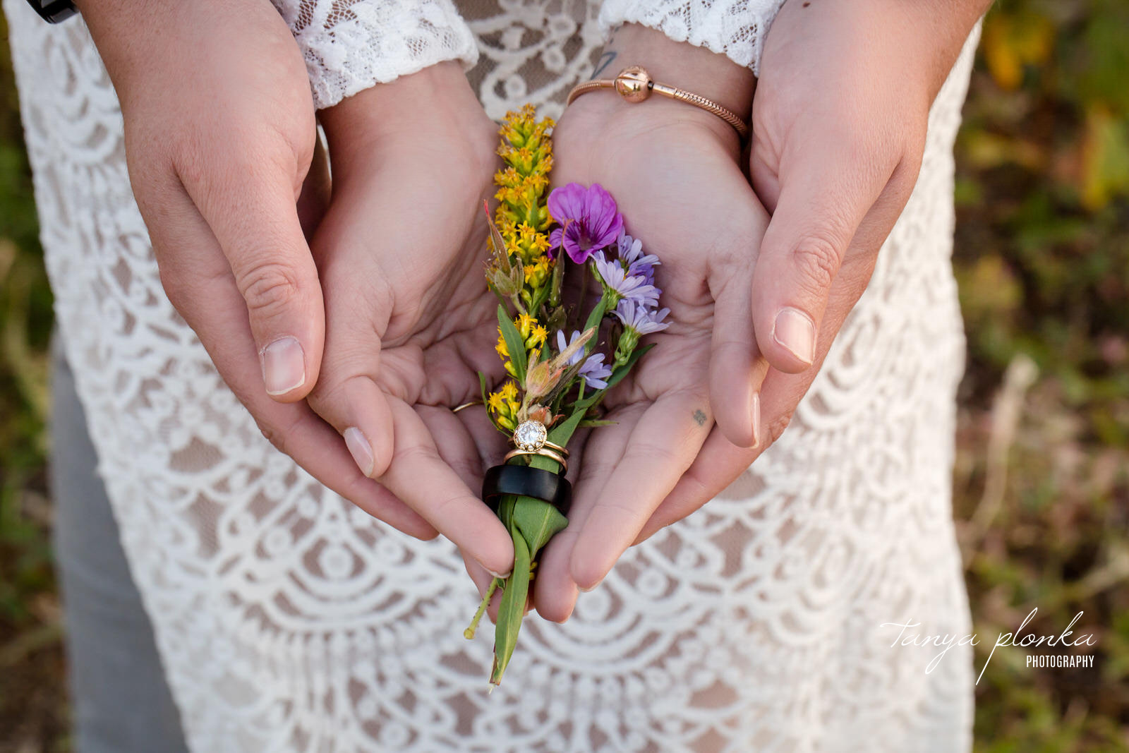 Bride's hands are placed in groom's hands as they hold wildflowers with wedding bands around the stems